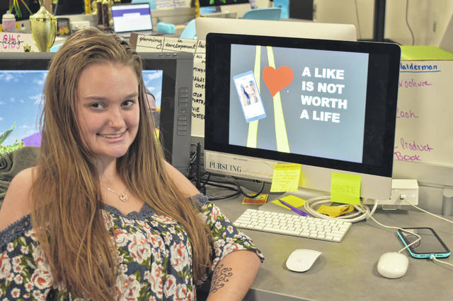 Delaware Area Career Center student Abbie Halderman poses next to her design that recently won SAFE Delaware's second annual billboard design contest for National Teen Driver Safety Week.