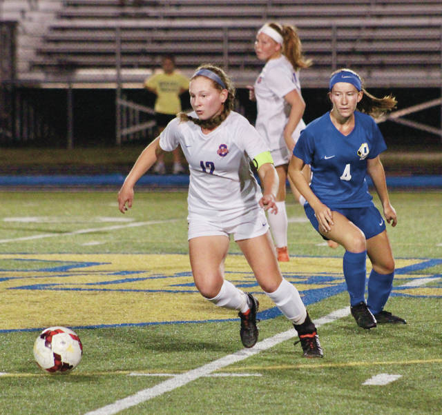 Olentangy Orange's Sophia Leonetti (12) collects the ball near midfield as Olentangy's Bailey Hall (4) looks on.