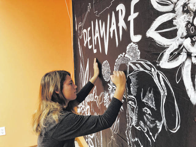Artist Natalie Smith paints on a canvas that will be displayed as a mural during today's First Friday celebration in downtown Delaware. Smith said she created the mural to show all kinds of things special to Delaware, including a horse, Rutherford B. Hayes, and the Bun's sign.
