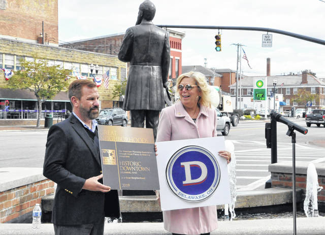 "Delaware Mayor Carolyn Riggle is all smiles Thursday afternoon after unveiling a replica of the bronze plaque that will soon be on permanent display in downtown Delaware. The plaque reads, ""The American Planning Association, through Great Places in America, designates Historic Downtown Delaware, Ohio as a Great Neighborhood."" Pictured holding the replica plaque is Chris Anderson, president of the APA's Ohio Chapter."