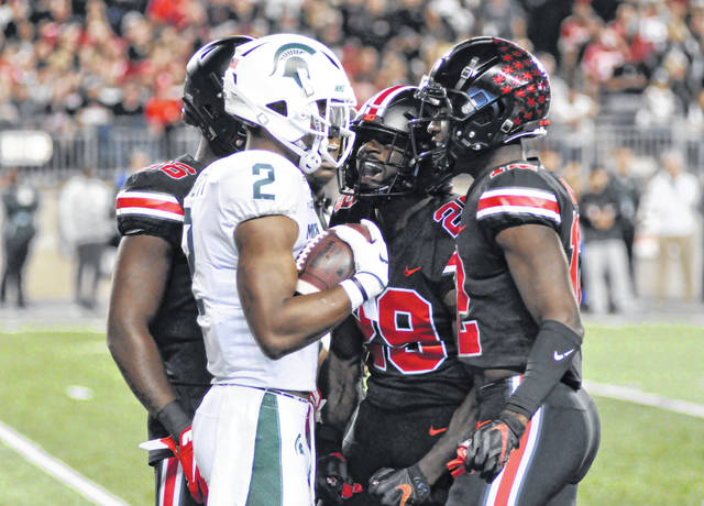 Ohio State's Marcus Hooker, middle, yells at Michigan State's Julian Barnett after he made a fair catch during Saturday's game in Ohio Stadium.
