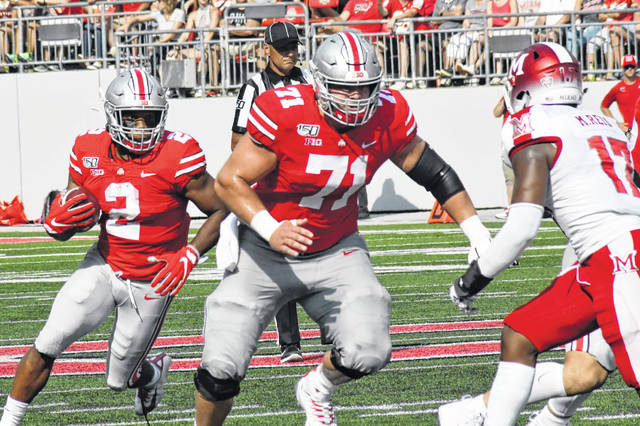Ohio State center Josh Myers leads the way for J.K. Dobbins during a Sept. 21 game against Miami.