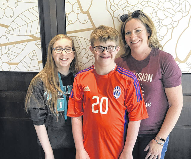 Alex Kearns (middle) and his family (sister Addie, left; and mother Jen, right) continue to champion the call for inclusion for those living with Down syndrome.