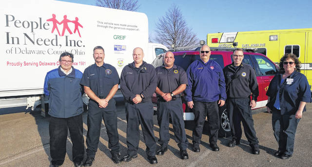 Representatives from People In Need, Meijer, Delaware EMS, the Delaware Fire Department, and the Tri-Township Fire District gather together in front of the PIN truck and an ambulance, both of which will be at the food drive Sunday. From left to right: PIN director Randy Bournique, Delaware Fire Department Fire Inspector Blaise Stojkov, DCEMS paramedics Dan Dixon and Michael Rezentes, Tri-Township Fire Chief Troy Morris, DCEMS Lt. Curt Hill and Meijer Administrative Assistant Paula Shults.