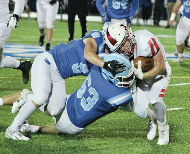 Olentangy Berlin's Jake Hill (63) and Corey Hill (9) combine to tackle Thomas Worthington's Nate Hoover during the first half of Friday's regular-season finale in Delaware.