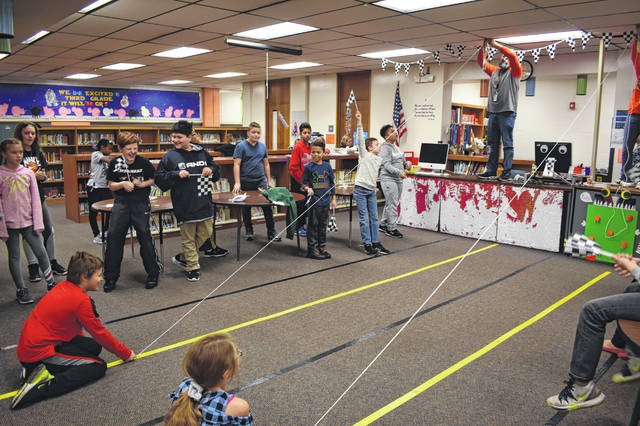 "Fifth grade students at Woodward Elementary School race ""turkeys"" Friday morning. Students were given a variety of materials to create their own turkeys to race down a zipline in the library."