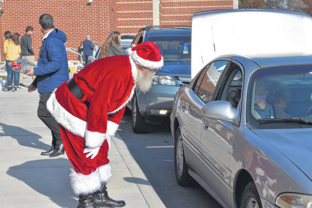 Santa Claus (Jon Martin) greets a family Tuesday during the fifth annual Hunger Games event at Hayes High School.