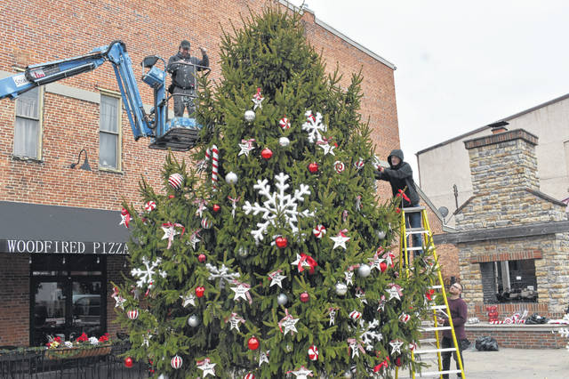 A crew from Steven Kline Productions hangs decorations and lights on the Christmas tree at the corner of William and Sandusky streets Friday morning in downtown Delaware. The tree is also decorated with stars adorned with names of businesses that are part of Main Street Delaware.