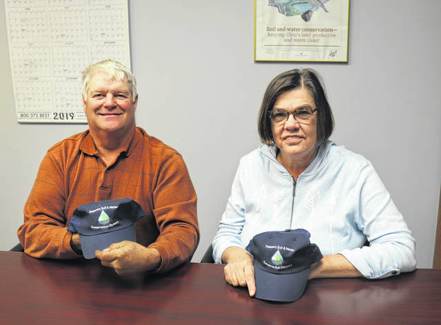 Ted Colflesh, left, and Sue Cunningham, right, show off Delaware Soil and Water Conservation District hats after being re-elected to three-year terms as board members of SWCD.