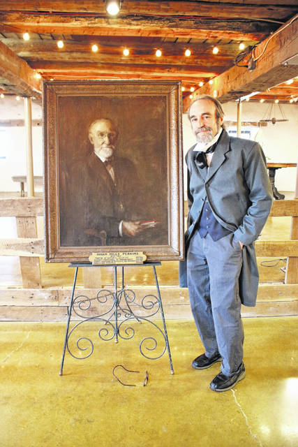 Tom Burns is pictured standing next to a portrait of Hiram Perkins.