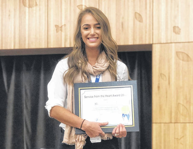 Marissa Garland, an athletic trainer at Nationwide Children's Hospital, is pictured with the Service From the Heart Award she was given earlier this year by the hospital. Garland was at the Delaware City Schools Board meeting Monday where she was recognized by the school board for saving the life of an assistant soccer coach.