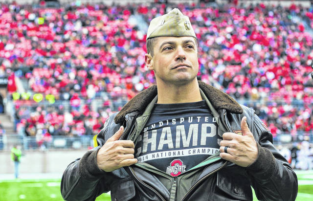 During Ohio State's Military Appreciation Day Nov. 9, Delaware native and Naval Aviator Lt. Sean Rooks led a small group of F-18 Hornets in a flyover before the Ohio State versus Maryland football game. About halfway through the third quarter, Rooks and his squadron appeared on the field during a timeout to wave to the crowd. Being the Buckeye fan he is, Rooks couldn't resist opening his jacket to reveal an OSU championship t-shirt underneath.