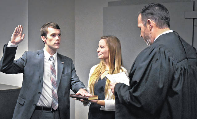 During a small ceremony Monday, Nov. 25, in the Delaware County Treasurer's Office, Michael Ringle raised his right hand while placing his left hand on the Bible that his wife, Emily Ringle, held as Judge James P. Schuck, Delaware County Common Pleas General Division, administered the oath of office.