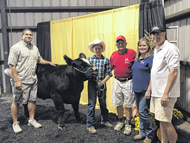 Trenton Wilson (wearing cowboy hat) and his family pose with Sticky at the Delaware County Fair. Trenton donated meat from the winning steer to the non-profit Big Walnut Friends Who Share in Sunbury.