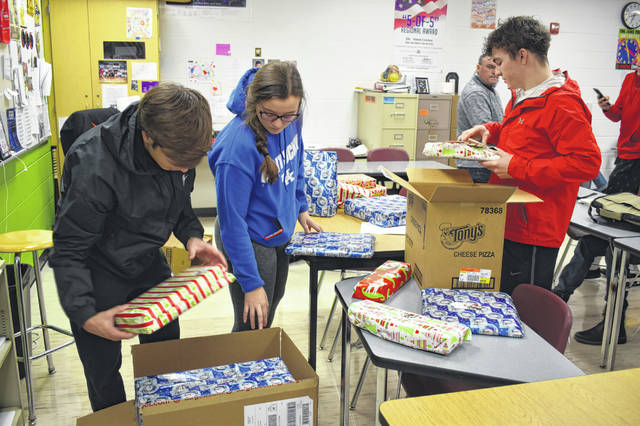 Students in the Jobs for America's Graduates (JAG) class at Hayes High School pack up presents to be delivered to a family earlier this week. Instructor Mark Thomas said this is the 15th year for the project.
