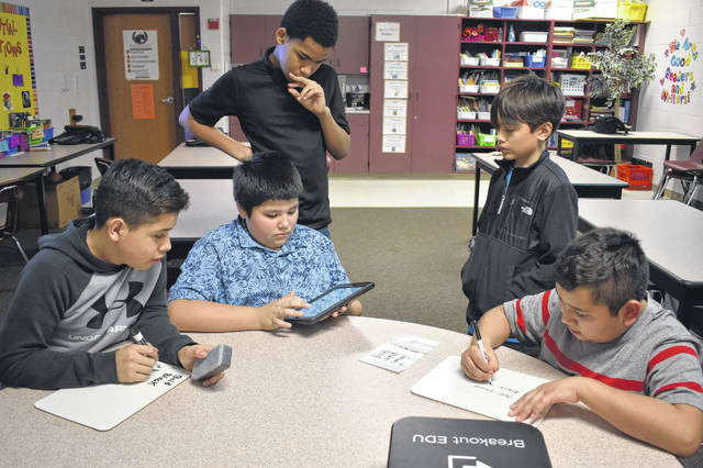 A team of students listen to samples of holiday songs to identify colors and open a digital lock on an iPad. Pictured, left to right, are Alejandro Olvera, Tony Rodriguez (in blue), Noa Wills (top left), Kaleb Watkins and Ryan Garcia.
