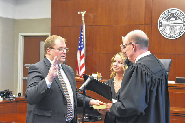 Judge-elect Kyle Rohrer is sworn in by outgoing Delaware Municipal Court Judge David Sunderman, with the help of Rohrer's wife, Erin, Dec. 20 in Delaware County Common Please Court. Rohrer will assume the role on Jan. 1.