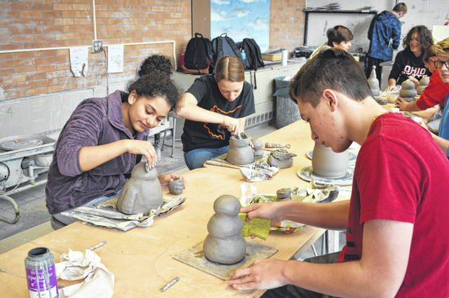 Kiah Gaston, left, Alana May, middle, and Braden Krauss, right, work on their snowman jars Friday afternoon at Delaware Hayes High School.