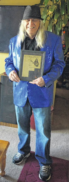 Moore holds a past Gazette article about himself.
