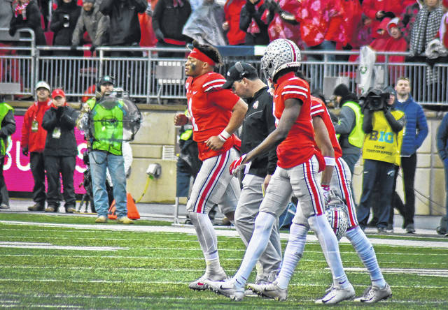 Ohio State head football coach Ryan Day walks off the field with the team's quarterback, Justin Fields, after he was injured during a play in the game against Penn State.