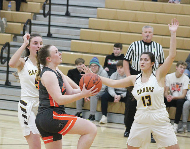 Hayes' Katie Smith drives to the hoop between Buckeye Valley's Dani Grether and Paige Garrett (13) during the second half of Monday's non-league showdown in Delaware.