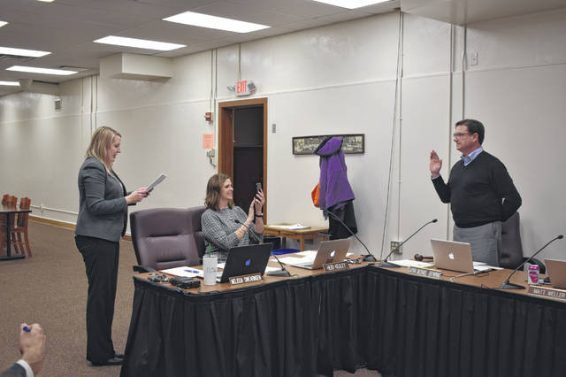 Delaware City Schools Treasurer Melissa Swearingen administers the oath of office to Matt Weller, who was elected board president for 2020. Weller has been on the board since 2008.