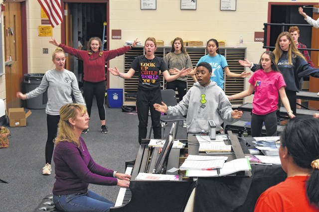 "Students stretch and warm up with musical director Dara Gillis Tuesday afternoon during a rehearsal for the upcoming production of ""Chicago."" The show will be performed March 19-21."