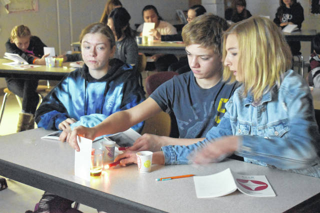 Seventh graders Natalie Heckert, Tommy Redmond and Anna Albrecht shine a light through three different liquids — dish soap, vegetable oil and corn syrup — to see how different liquids allow the light to pass through at different intensities. Cleveland Clinic instructors led the experiment.