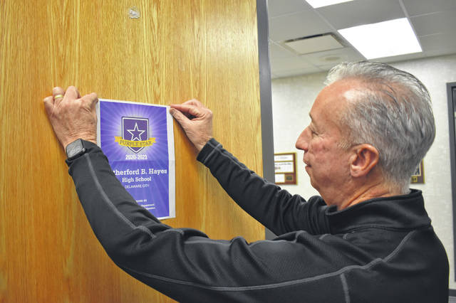 Hayes High School Principal Ric Stranges hangs up a notice designating the school as a Purple Star school. The designation came with a letter from the Ohio Department of Education, applauding the school for the work it did since last fall to assist and aid students with family members in the military.