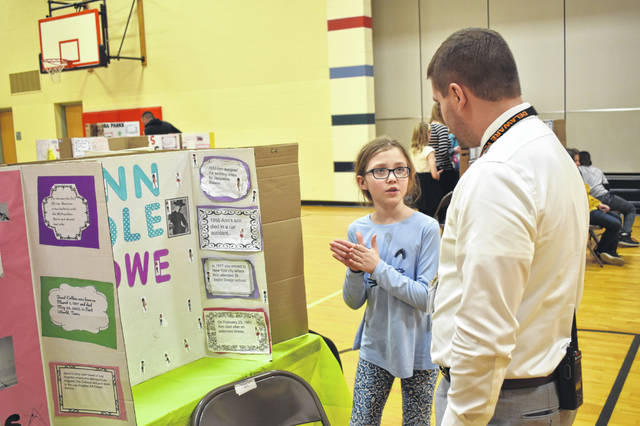 Conger fourth grader Evelyn Wengstrom shows off her project about African American fashion designer Ann Lowe to Conger Principal Josh Page Wednesday afternoon during Conger's Black History Month showcase.