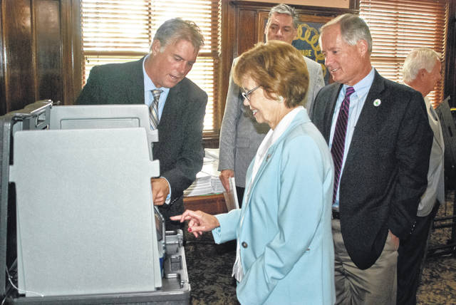 In a special work session held Aug. 20, 2018, before the new voting equipment was purchased, Jay Perbix (left), RBM Consulting election consultant, shows Commissioner Barb Lewis (middle) the ease the touchscreen offers in selecting candidates and issues on election day, while Commissioner Jeff Benton (right) closely watches the demonstration.