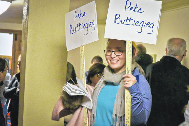 Acting as a wrangler for Ohio's 12th Congressional District Democratic Delegate Caucus 2020 Tuesday evening, Cara Posey leads a group of Pete Buttigieg supporters to a predetermined space to begin voting for delegates.