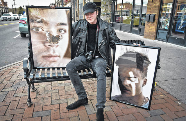 Austin Tolliver sits along East Winter Street in downtown Delaware holding two pieces of his recent work. Tolliver is holding the first public showing of his work from 7-9 p.m. Jan. 17 at Gather, 53 N. Sandusky St., Delaware.