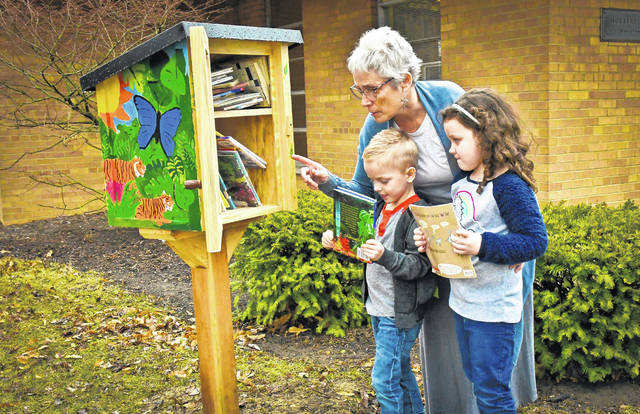 Charity Romero Rose, pre-K teacher at the Early Childhood Center at Ohio Wesleyan University, shows Oliver Almond, left, and Maddie Johnson, right, how the Little Free Library works.