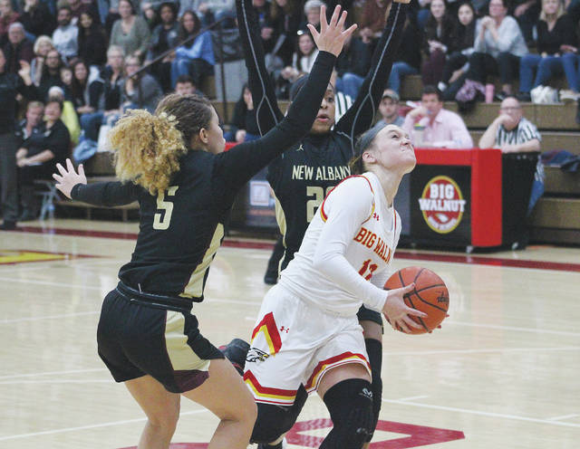 Big Walnut's Avery Schone slices between New Albany's Brooklyn Gammon (5) and Haley Dennis on her way to the hoop during the second half of Friday's OCC showdown in Sunbury.