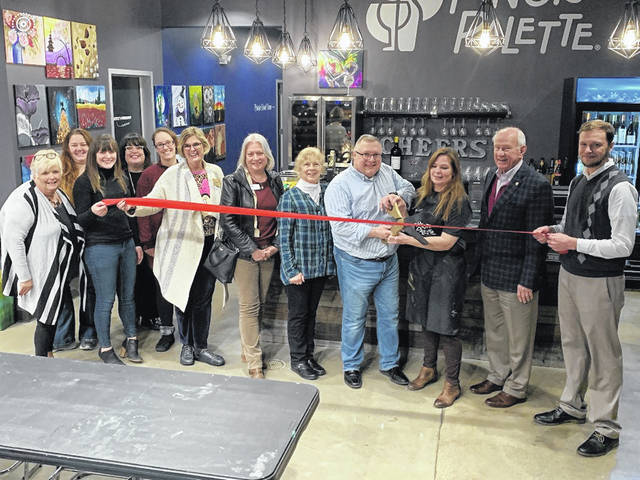 Pinot's Palette owners Eric and Shannon Hubbs (holding the scissors) cut the ribbon during the business' grand opening celebration Jan. 16 in Powell.