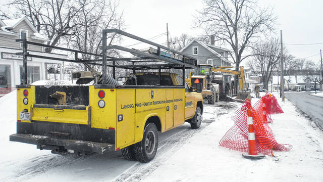A crew digs at the corner of Cherry and Columbus streets in Sunbury on a snowy Thursday morning to construct a new parking lot.
