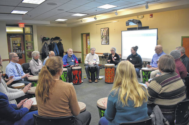 Central Ohio Symphony Executive Director Warren Hyer (center in white) leads a group of community members and leaders in a drum circle exercise Wednesday at the Delaware County District Library in Delaware. Hyer's drumming program works with juveniles in drug, alcohol or behavior cases from Delaware Juvenile Court.