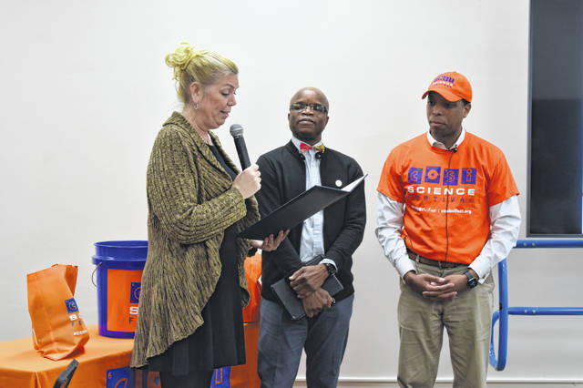 """Delaware Mayor Carolyn Riggle reads a proclamation for Tajudeen Bakare (middle), a Delaware resident and engineer, who was selected as a """"STEM Star"""" and will be one of the grand marshals for the upcoming COSI Science Festival."""
