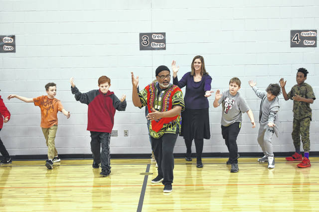 Delaware resident and tai chi instructor Mark Butler leads students and Delaware Superintendent Heidi Kegley in a tai chi movement called a palm strike during a class held Thursday at Woodward Elementary.
