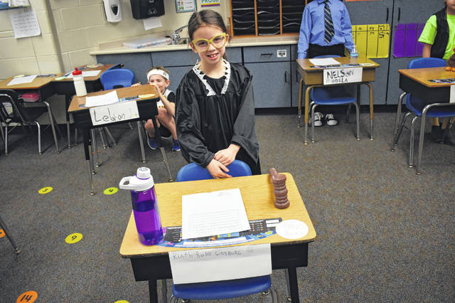 "A ""wax figure"" of U.S. Supreme Court Associate Justice Ruth Bader Ginsburg, played by second grader Charlotte Turay, stands ready to give a presentation about the justice's life Tuesday morning during the ""wax museum"" event at Carlisle Elementary School in Delaware."