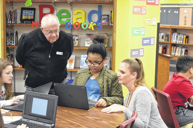 Woodward Elementary librarian Robyn Kress, right, and Delaware County Historical Society President Emeritus Brent Carson, left, help Amira Lewis, a fourth grader, find the right book with a clue about her subject.