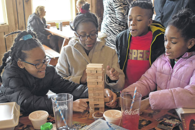 Leia Riley, Chace Riley, Reggie Hopkins and Ryan Hopkins play Jenga while waiting for their food Saturday. The event also featured games, music and prizes from local teacher Francine Butler, who asked questions about figures from local African American history.