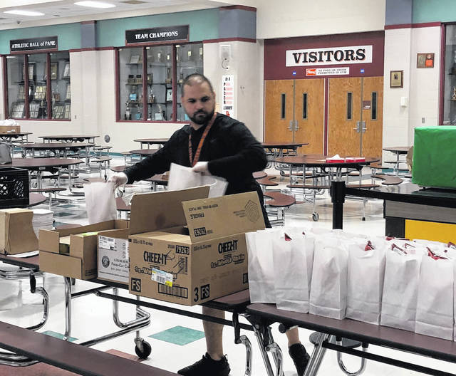 Justin Malivuk, a health and P.E. teacher at Dempsey Middle School and Hayes High School, packs grab-and-go lunches Monday.