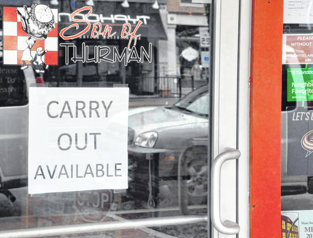 Carryout signs like this one at Son of Thurman on North Sandusky Street have been posted to storefronts around downtown Delaware following the governor's ban on patrons dining in at their favorite establishments.