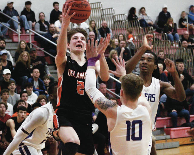 Delaware Hayes' Nate Griggs puts up a shot between a trio of Pickerington Central defenders during the second half of Wednesday's Division I district semifinal.