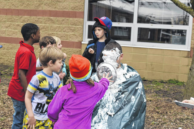 Page takes a pie pan full of whipped cream to the face in April 2019 as a reward for students reaching their read-a-thon goals.