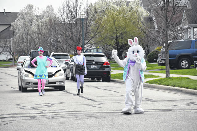 The Easter Bunny, McNamara, and Giesler parade down Rockmill Street waving to families standing on their porches or in their yards.