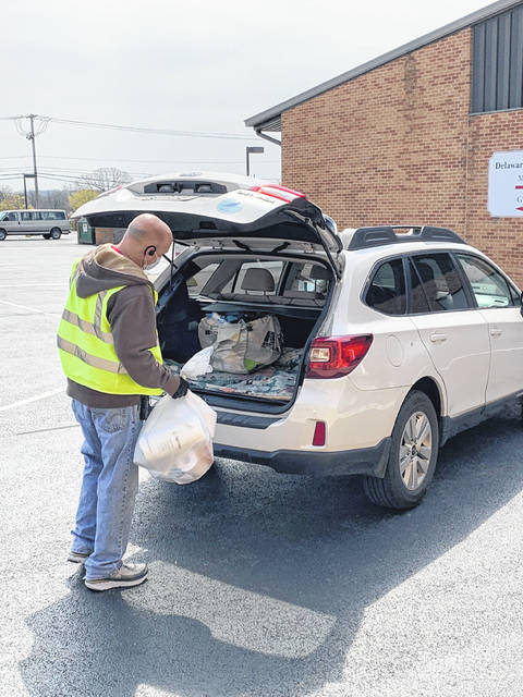 """Donald Burroughs loads a """"blessing bag"""" into a car during Delaware Bible Church's drive-thru service Saturday morning."""