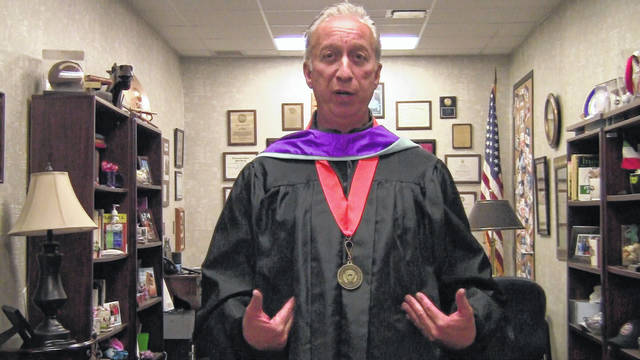 Hayes High School Principal Ric Stranges address students in his commencement robe in a video this week. In the video, Stranges said the school plans to have a procession where students will travel in their vehicles to Hayes and receive their diplomas without having to make physical contact with anyone.